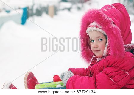 Little Girl In Red Warm Clothes Smiles And Looks At Camera At Winter Day