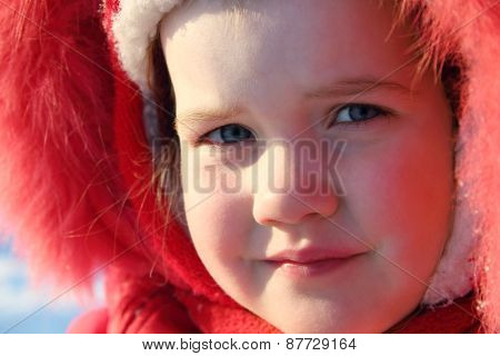 Little Girl In Red Warm Fur Hood Looks At Camera At Winter Sunny Day