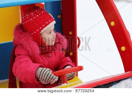 Little Happy Girl In Red Warm Clothes Sits In Car On Playground At Winter Day