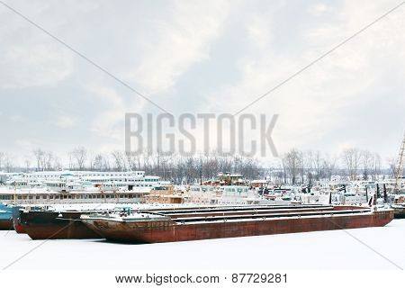 Old And Rusty Big Freight And Passenger Ships On Frozen River At Winter Cloudy Day