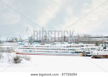 Big Tourist Liner And Other Ships On Frozen River At Winter Snowy Day