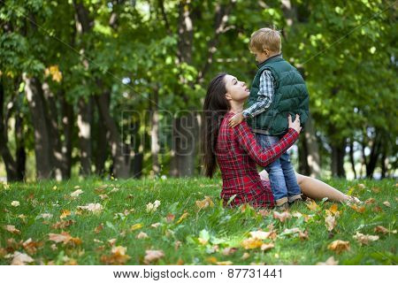 Young beautiful mother hugging her son in the autumn park