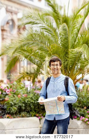 Smiling young man in glasses with touristic map and backpack resting during excursion on vacation
