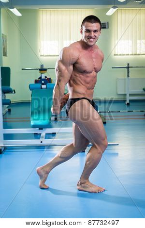 Bodybuilder man posing in GYM