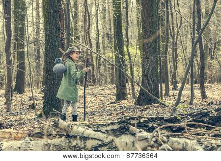 smiling little girl goes through the woods. Photo in retro style