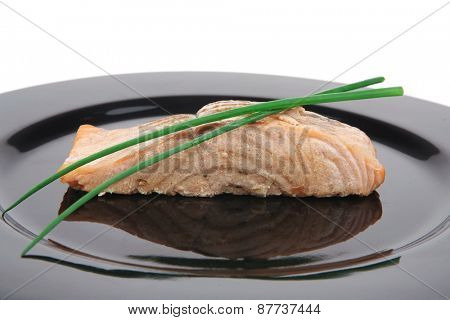 savory fish portion : norwegian salmon fillet roasted with green chinese onion, on black dish isolated over white background