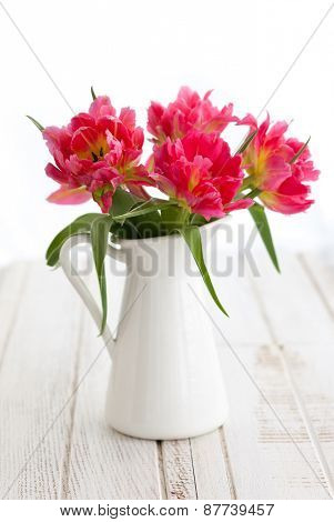 Beautiful pink double peony tulip in vase on the wooden table