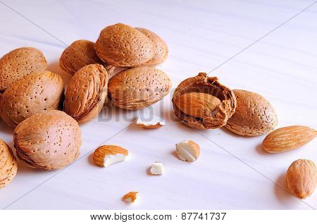 Almonds In Shell And Shelled On A White Wooden Table