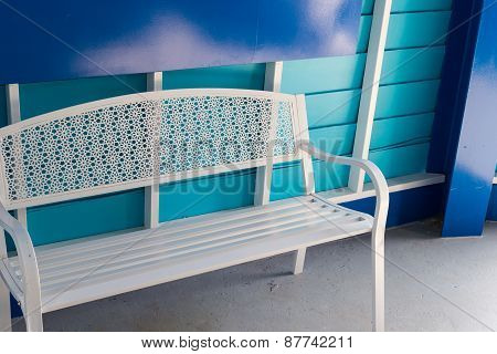 White Metal Seat Beside Blue Wall