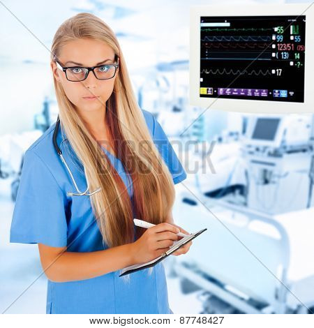 Young female doctor writing prescription in ICU with medical equipment on background