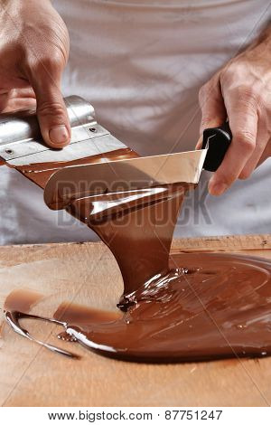 Cook mixing chocolate cream with professional chocolate spatula. Melted dark chocolate.