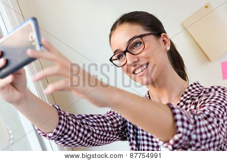 Beautiful Young Woman Using Her Mobile Phone In The Office.