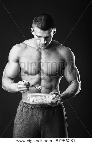 Male bodybuilder posing on a dark background