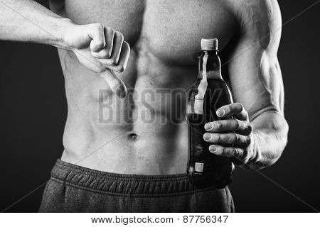 Male bodybuilder shows that beer is bad. Unhealthy eating habits