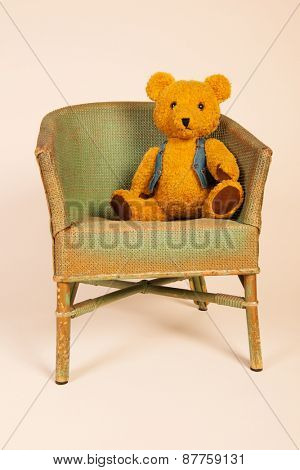 Stuffed bear sitting in old vintage chair