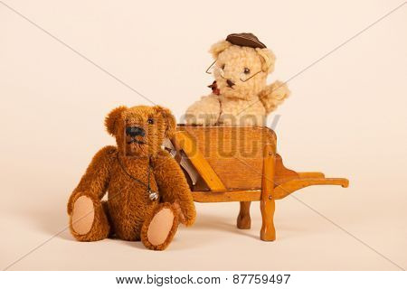 Stuffed bears in vintage wheel barrow isolated over white background