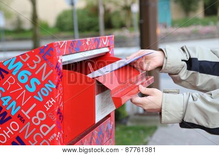 Coquitlam, BC Canada - April 24, 2014 : Hand sending a tax report letter in a red mail box