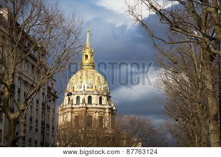Sunlight hits the golden dome of L'Hotel national des Invalides with dramatic stormy sky, Paris, France