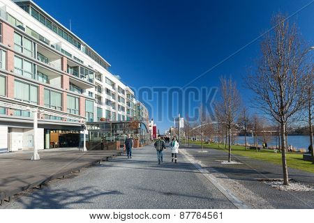 BRATISLAVA, SLOVAKIA - JANUARY 6, 2015: People on walkway next to shore of Danube river with Apollo bridge in the background.