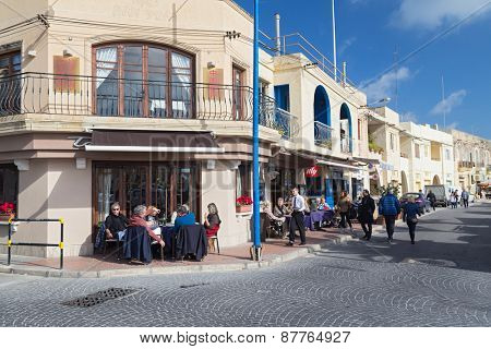MARSAXLOKK, MALTA - JANUARY 11, 2015: People sitting at cafe  terrace near the Parish Church of Our Lady of Pompei.