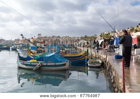 MARSAXLOKK, MALTA - JANUARY 11, 2015: Fisherman at the dock next to Marsaxlokk market, one of the city's main features especially on Sunday.