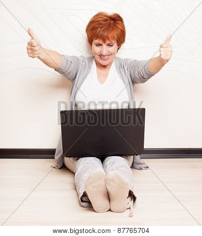 Woman sitting on floor with laptop. Mature female at home