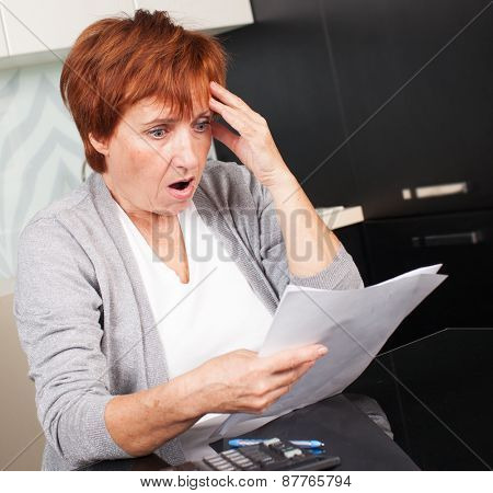 Sad businesswoman with document. Elderly woman sorting through her old receipts at home.
