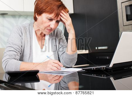 Sad businesswoman with document. Female sorting through her old receipts at home.