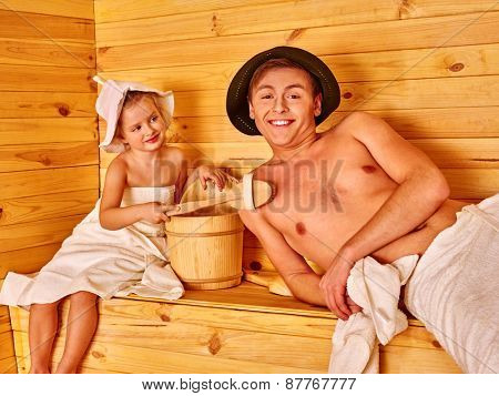 Happy family with child relaxing at sauna. Father and daughter.