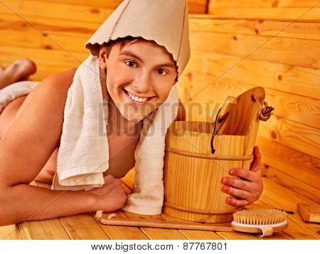 Man in hat  relaxing at sauna. Male with towel lying on wooden boards