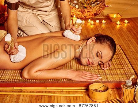 Woman getting herbal ball massage by candlelight in spa. Eyes are close.