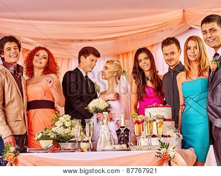 Group people at wedding table with cake. In the center of bride and groom