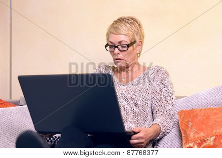 Serious Middle Age Woman On Sofa With Laptop