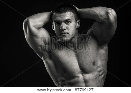 Black and white photography. Handsome muscular guy, bodybuilder, posing on a black background.