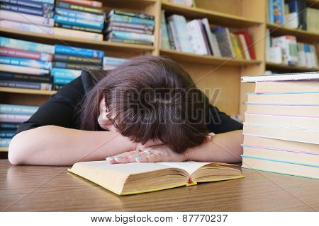 Tired student girl sleeping on the book in the library