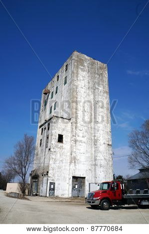An old grain elevator with a truck parked in front