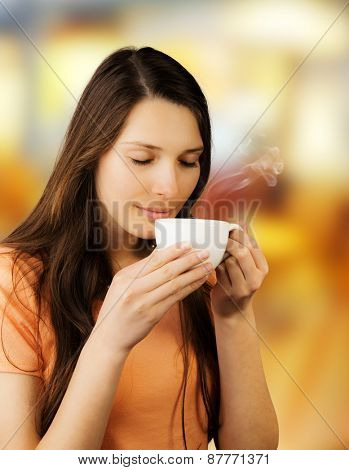 Attractive young brunette woman holding cup of coffee and enjoying smell of drink