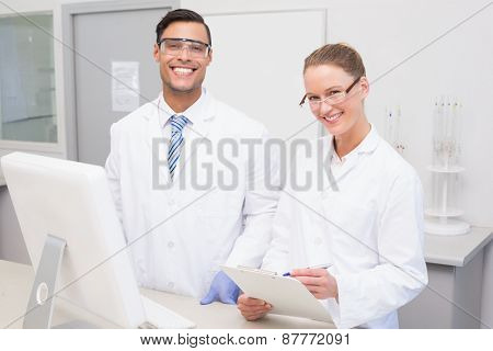 Happy scientists smiling at camera in the laboratory