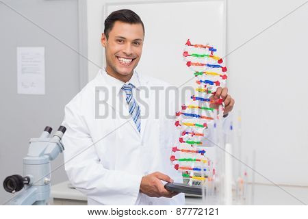 Happy scientist smiling at camera with DNA helix in the laboratory