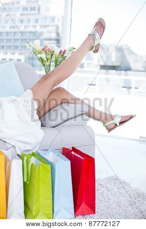 Brunette lying on the couch with shopping bags around her in the living room