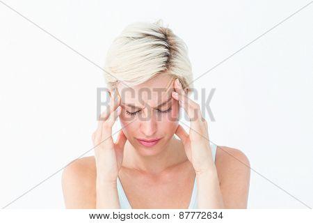 Pretty blonde suffering from headache on white background