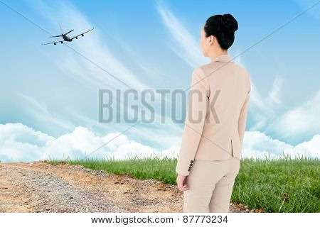 Asian businesswoman walking against road leading out to the horizon