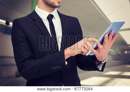 Mid section of a businessman using digital tablet pc against airport