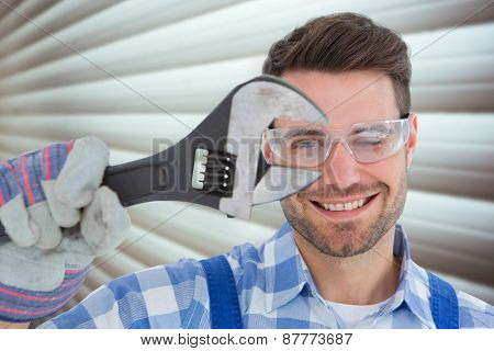 Confident repairman wearing protective glasses while holding wrench against grey shutters