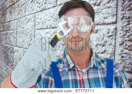 Plumber holding adjustable wrench against grey brick wall