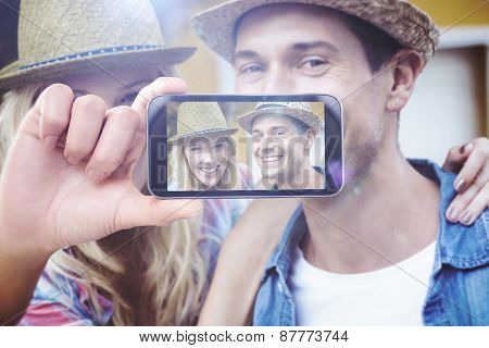 Hand holding smartphone showing against hip young couple smiling at camera