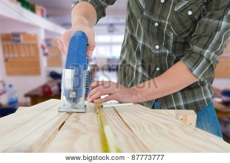 Carpenter cutting wooden plank with electric saw against workshop