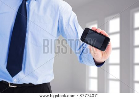Close up of businessman holding a phone against dark white room