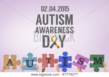 Hands holding up autism jigsaw pieces against purple vignette