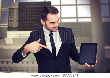 Happy businessman pointing with his tablet against airport